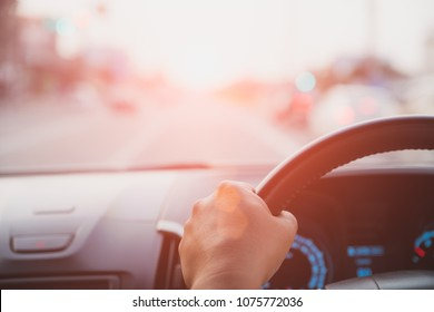 Soft focus driver hand holding steering wheel while driving on the road.