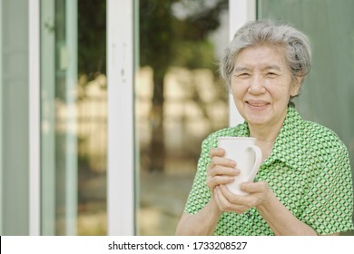 Soft focus at elder Asian women smile and drinking hot milk at home. Healthy senior woman holding a glass milk. Happy elderly enjoy with tea. Healthy people, Tea Time, Aging society and insurance