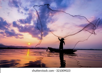 Soft focus and  Fisherman of Bangpra Lake in action for fishing Thailand.