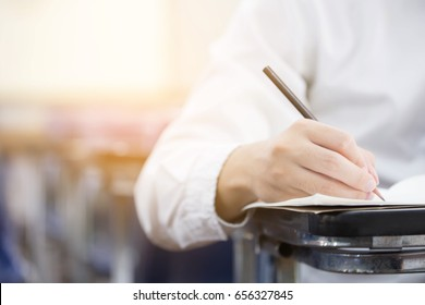 soft focus front view undergraduate holding pencil writing on paper answer sheet and sitting on lecture chair doing final exam attending in examination room or classroom.university student in uniform.