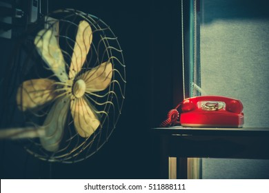 Soft focus of gold vintage fan and  red vintage telephone on wood floor.vintage retro concept with film grain
