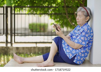 Soft focus at grandmother relaxing and taking selfie on smartphone in the garden, Elderly Asian woman reading good news, sharing with friends in social network. Concept technology with senior people.
