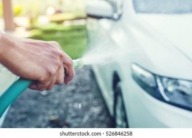 Soft focus hand holding car wash hose