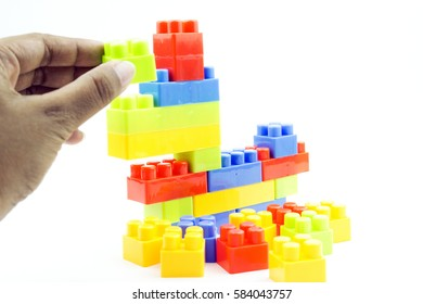 Soft focus of hand holding plastic building block over white isolated background