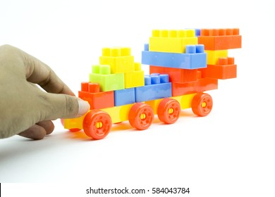 Soft focus of hand holding and playing plastic building block over white isolated background
