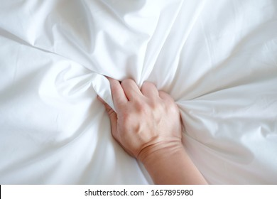 Soft focus hand of women holding bedclothes. Hand sign orgasm of woman on white bed , Hand of female pulling white sheets in ecstasy. love climax women sex on bed. Concept sex and feel good.