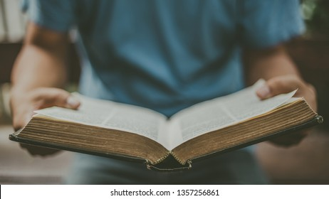Soft Focus of hands man open the old holy bible with copy space,Sunday reading concept.