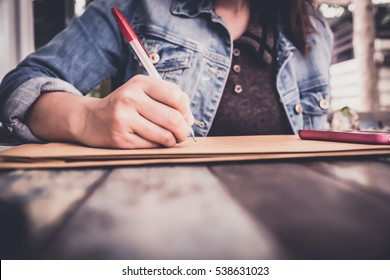 soft focus hands of a young woman as she is writing letter and notepad Or something on a wooden table . Customize colors Vintage retro and old film Tone .