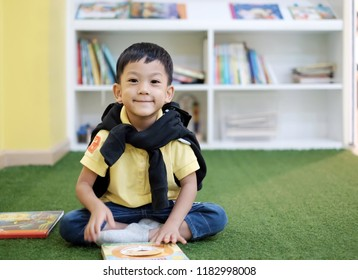 Soft focus at handsome Asian kid smile and look at camera. Little Asia boy sit in library room and read a book background with bookshelf. Concept self learning, Smart and genuine kid, Test examination