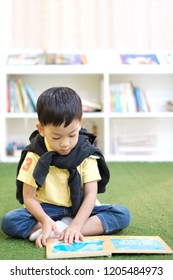 Soft focus at handsome Asian kid reading a book. Little Asia boy sit in library room and read a book background with bookshelf. Concept self learning, Smart and genuine kid, Test examination