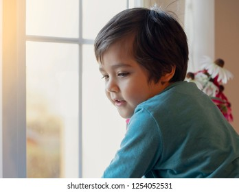 Soft focus Happy boy standing next to window with smiling face, Cute kid with happy face looking down, Side view Child wearing pyjama playing near window with bright light in the morning,