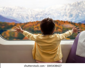 Soft Focus of Happy and Excited Kids Traveling by Train with her Family during Autumn and Winter Season. a Girl Looking through Wide Glass Window. Moutain with Snow as Outside View