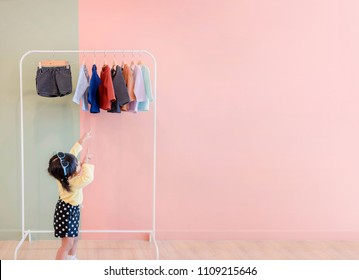 Soft Focus of Happy Kids Pointing her hands to Cloth Rack for Choosing own Dresses