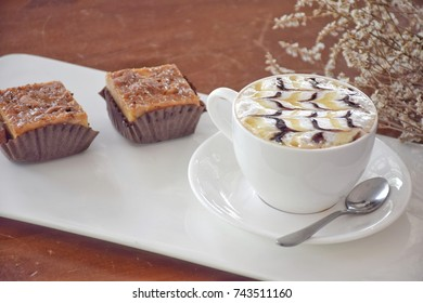 Soft focus of hot caramel macchiato coffee in cup and toffee cake served on white dish vintage concept