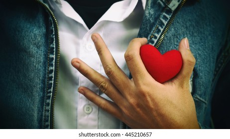Soft focus human hand holding red heart shape for love and good healthy concept, valentine day and romance background
