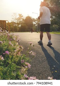 Soft focus Jogging old man running in park along road with flowers during morning sunrise. Jogging for health concept.