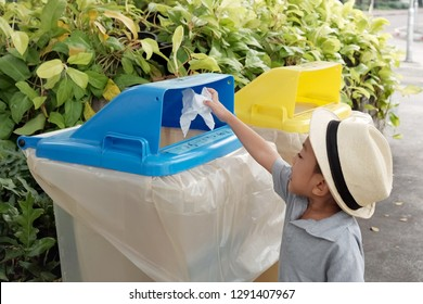 Soft focus at little Asia kid 4 year old try to throw the tissue paper in public blue trashcan for sorting garbage and recycle the paper. Concept of Sorting garbage, Recycle environment, save world.