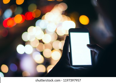 Soft focus man using his mobile phone in the street, night light bokeh Background,copy space.