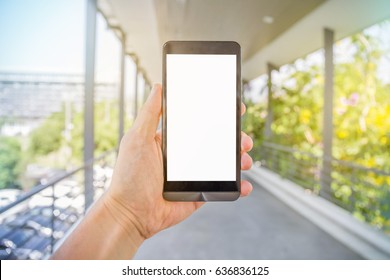 soft focus Man's hand holding mobile,smart hone with blank screen for text vertical position, outdoor public park,linking the sky,tree,car,building blurred background. concept for business,commercial.