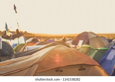 soft focus music festival camping concept view with a few tents  in evening sunset colorful orange time and sun glares
