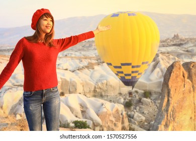 Soft focus on asian woman standing on fantastic landscape with hot air ballons in early moning at Cappadocia, Turky