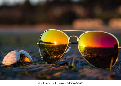 Soft focus on aviator sunglasses & seashell with reflection of beautiful colorful sunrise in horizon