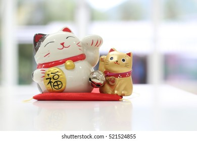 Soft focus on couple of Japanese ceramic figurine cats, one is white with left beckoning paw the other gold one with right beckoning paw which both means good luck for business and home