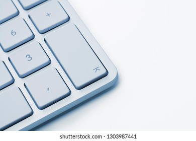 Soft focus. Focus on the enter key of a white keyboard against white background.