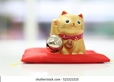 "Soft focus on a golden ceramic Japanese figurine cat beckoning with right upright paw,  red neckerchief, silver bell and gold coin red letter ""senmanry?"" means ten million ryo to bring good luck"