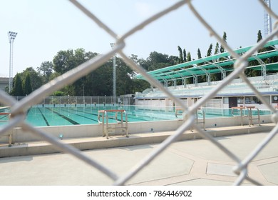 Soft focus on metal net, see through outdoor swimming pool with sunny day sky .