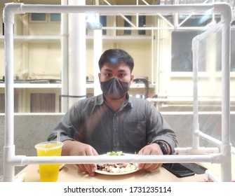 Soft focus on Partition on front of man wearing masks were eating lunch with partition for prevent airborne contamination in a viral epidemic situation, Social Distancing and New normal concept.