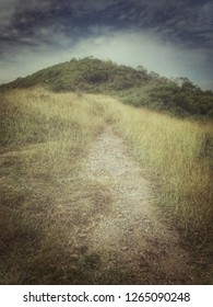 soft focus pathway to the top of mountain, scenery of grass field high hill with walk way in cloudy dark sky weather