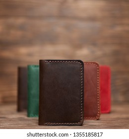 Soft focus photo of brown colour handmade leather cardholder. Blurred background on photo. Different colour cardholders blurred on background.