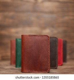 Soft focus photo of ginger colour handmade leather cardholder. Blurred background on photo. Different colour cardholders blurred on background.