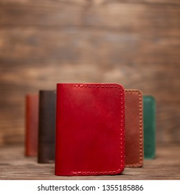 Soft focus photo of red colour handmade leather cardholder. Blurred background on photo. Different colour cardholders blurred on background.