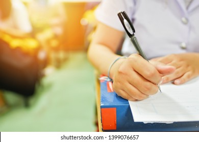 Soft focus picture; student writing note or taking test in the classroom for the midterm or final examination; education concept picture of learner in studying room doing assignment given by teacher