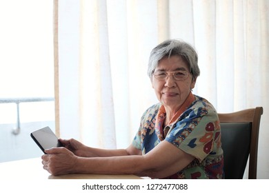 Soft focus and portrait at Asian elderly women smiling and sitting on desk and  playing tablet. Concept of happy elderly people , Senior activity and retirement , technology with old people.