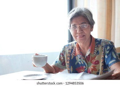 Soft focus and portrait at Asian elderly women smiling and drinking coffee and  reading newspaper. Concept of happy elderly people , Senior activity and retirement, tea time, business with old people.