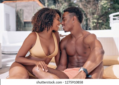 Soft focus portrait of a loving African American couple sitting near the swimming pool and kissing. Phuket. Thailand. Trip to warm destination