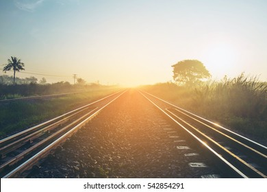 Soft focus Railroad against beautiful sky at sunset. Industrial landscape with railway station, colorful blue sky with clouds, trees and green grass, yellow sunlight.