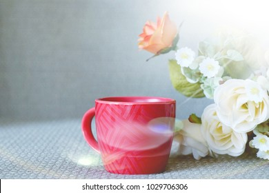 soft focus red cup of coffee with white and orange rose flower, wall blurred background.