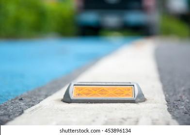 soft focus of reflector or stud on asphalt road