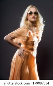Soft focus retro hippie 70s fashion sensual girl with long blonde hair wearing an orange dress and sunglasses. Studio shot against grey.