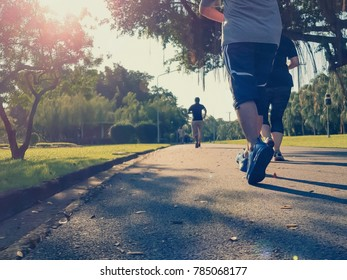 Soft focus runner man and woman running in park with green grass along road in sunrise morning