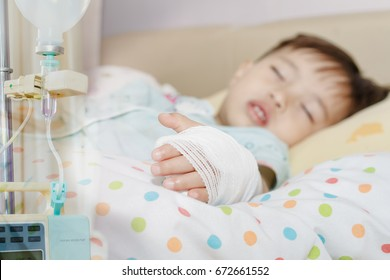 soft focus Saline intravenous (iv) drip in a Children's patient hand,kid sick and sleep and equipment IV tube of Infusion pumps for patients in hospitals