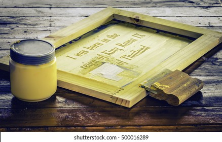 Soft focus Screen printing squeegee on silk screen frame and yellow ink