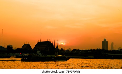 soft focus of The silhouette of the temple and the boat in the river. In the light of the morning sun.