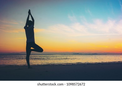 Soft focus Silhouette young woman practicing yoga on the beach at sunset selective focus.