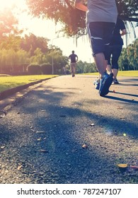 Soft focus sport runner man running in park with green grass along the road against sunrise