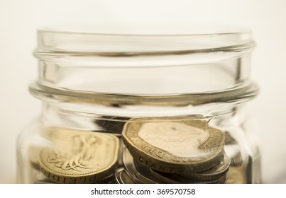 Soft focus stack of coins in glass jars